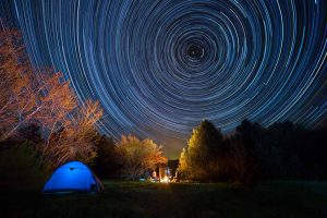 Retreats in Everyday Life: Tourist tent against the night sky with tracks from stars