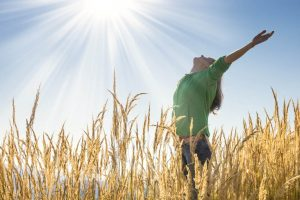 Retreats in Everyday Life: Happy young girl raising her arms with bliss and joy in the tall grass on a beautiful sunny day