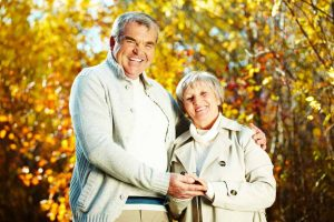 Retreats in Everyday Life: Photo of happy aged man and woman looking at camera in autumnal park